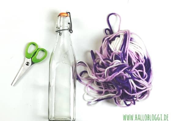 Eine Glasflasche mit Wolle verschönern. Mehr Ideen auf Hallo Bloggi www.hallobloggi.de