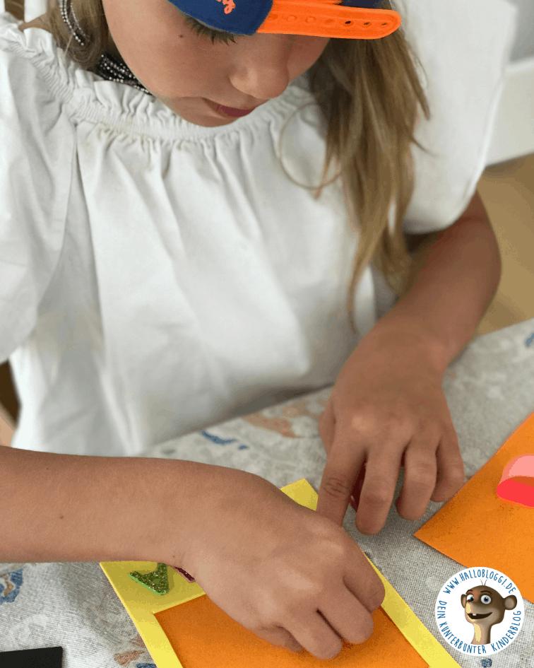 Kind bastelt Bilderrahmen für die Mama